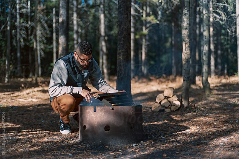 A young bearded man tends to a fire pit while camping. by Riley J.B. for Stocksy United