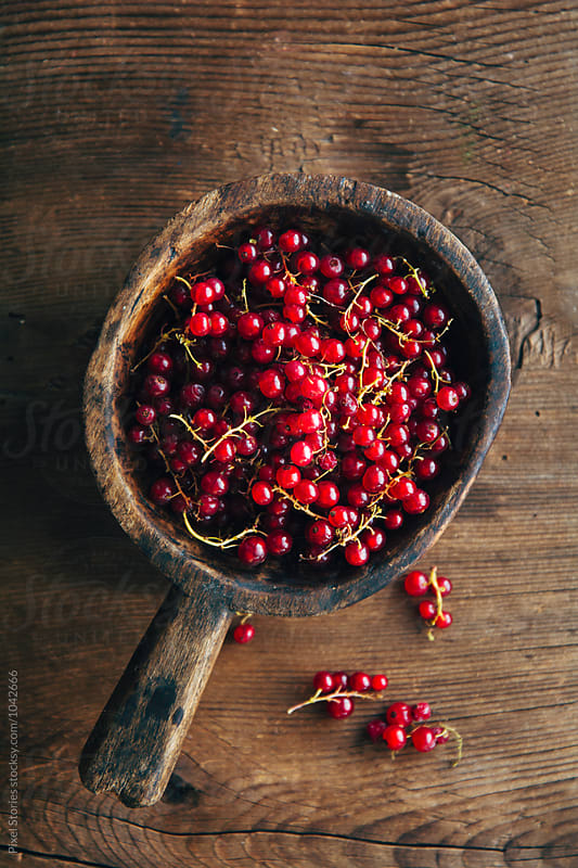 Fresh picked red currants in rustic wooden bowl by Pixel Stories for Stocksy United