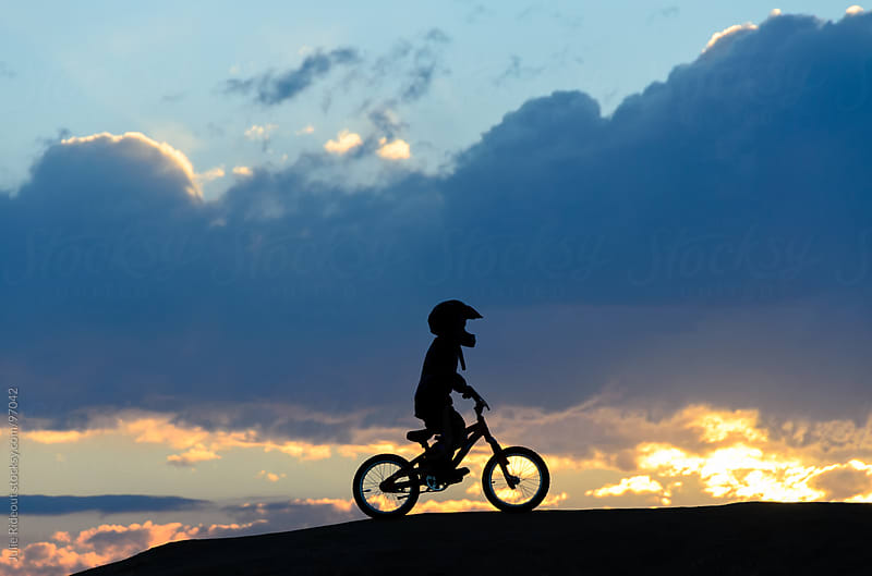 Boy Riding BMX bike at sunset by Julie Rideout for Stocksy United