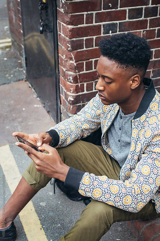 Overhead Shot of Young Fashionable Black Man Using Cellphone in London Street by VISUALSPECTRUM for Stocksy United