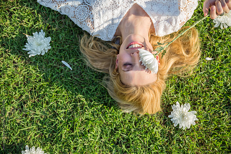 Beautiful smiling blonde lying on grass and covering her eye with a white flower  by Jovo Jovanovic for Stocksy United