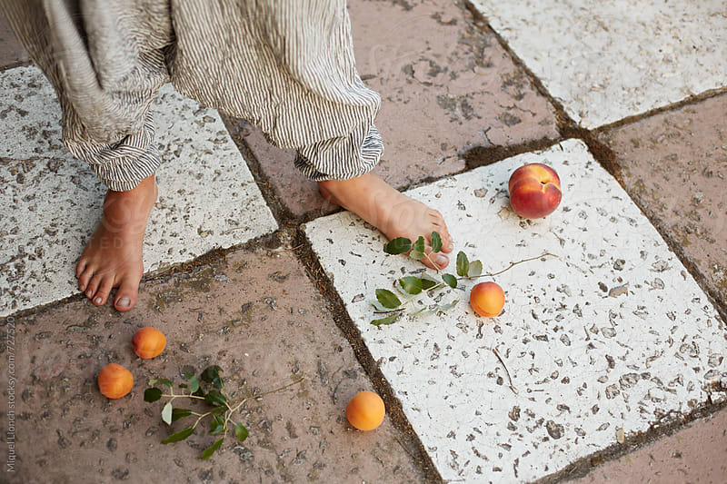Feet and fruits on an beautiful background by Miquel Llonch for Stocksy United