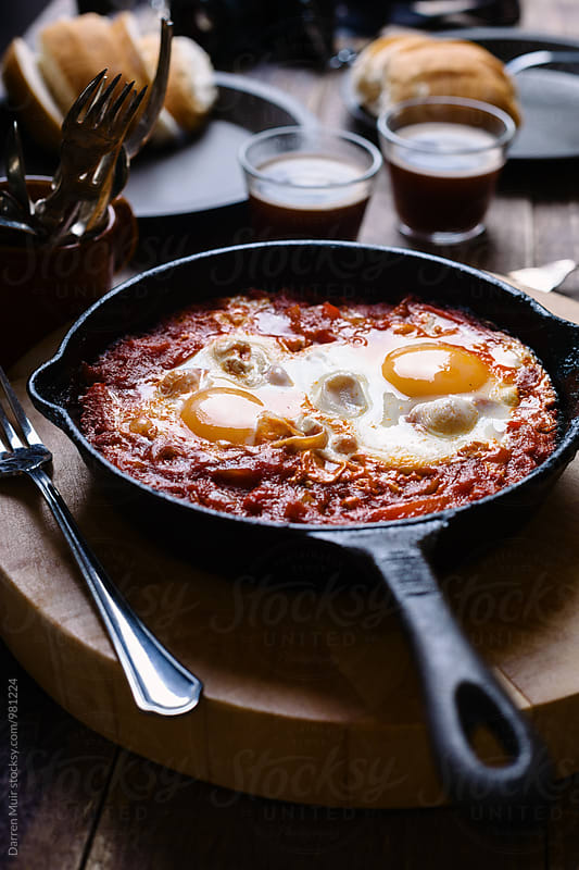 Shakshouka or shakshuka in a cast iron skillet. by Darren Muir for Stocksy United