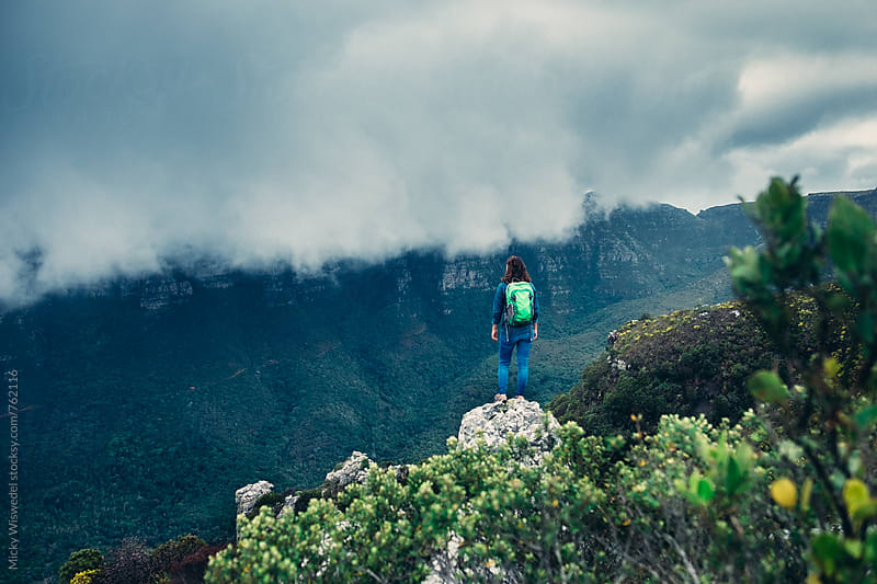 Female hiker on a rocky outcrop overlooking a stormy mountain view by Micky Wiswedel for Stocksy United