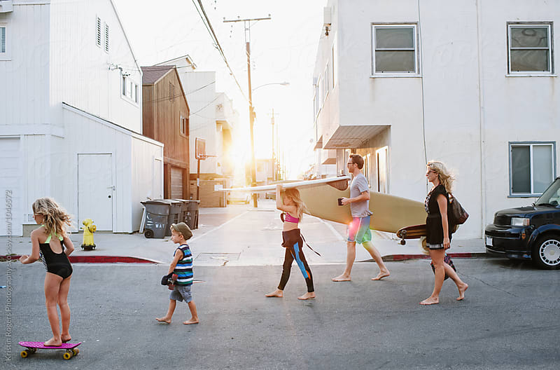 Family of five walking and skateboarding to beach through street by Kristin Rogers Photography for Stocksy United