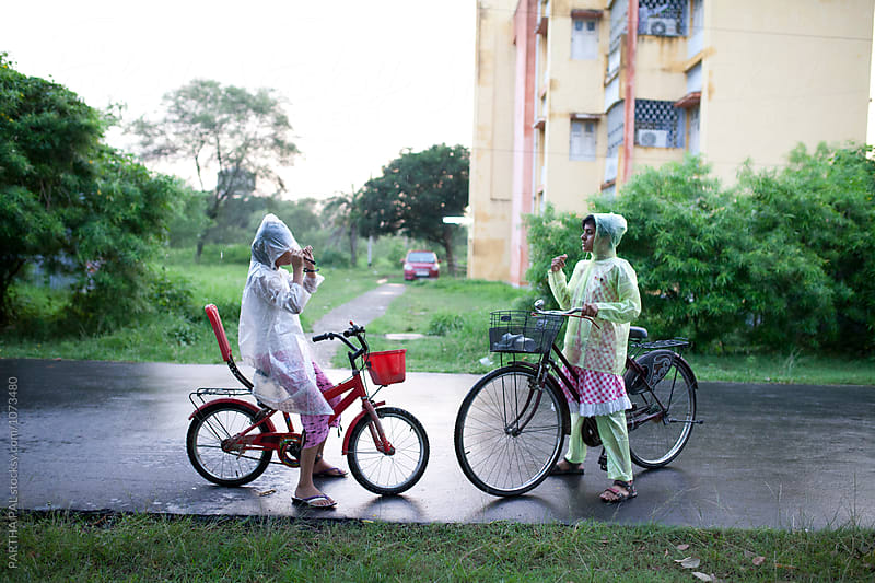 Teenagers wearing Rain coat and gossiping by PARTHA PAL for Stocksy United
