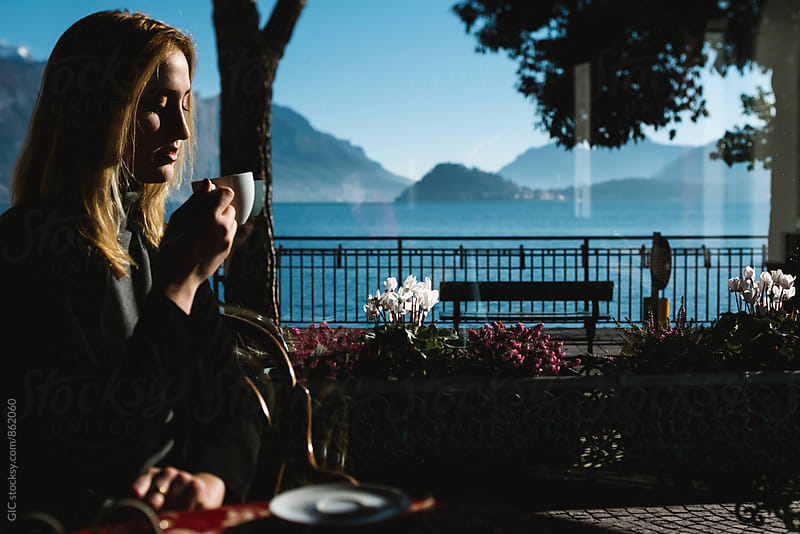 Young woman taking a coffee on the Lake Como by Simone Becchetti for Stocksy United