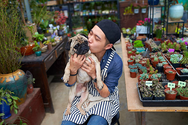 male florist holding his dog in the shop by Bo Bo for Stocksy United
