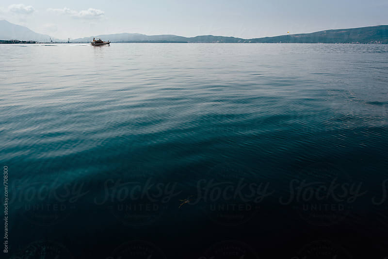 Boat sailing in calm waters by Boris Jovanovic for Stocksy United