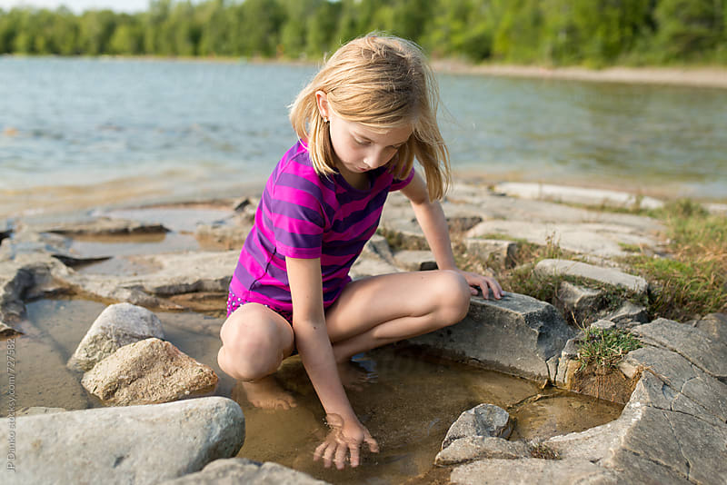 Little Girl Playing In Puddle on a Rocky Northern Cottage Lakeshore on Warm Sunny Summer Day by JP Danko for Stocksy United