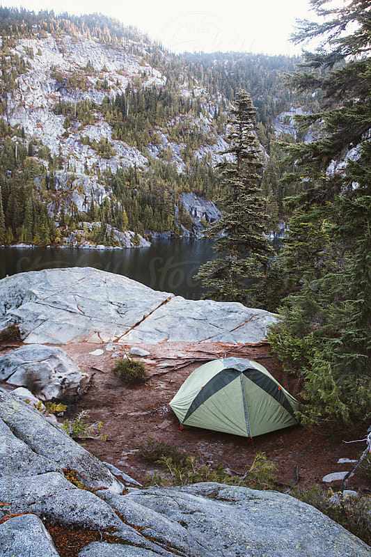 Green Tent Pitched Among Granite Boulders Near Lake In Subalpine Forest by Luke Mattson for Stocksy United