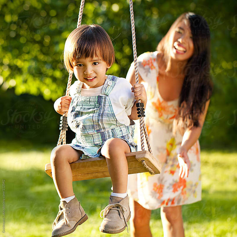 Smiling Asian Boy on a Swing by Goldmund Lukic for Stocksy United