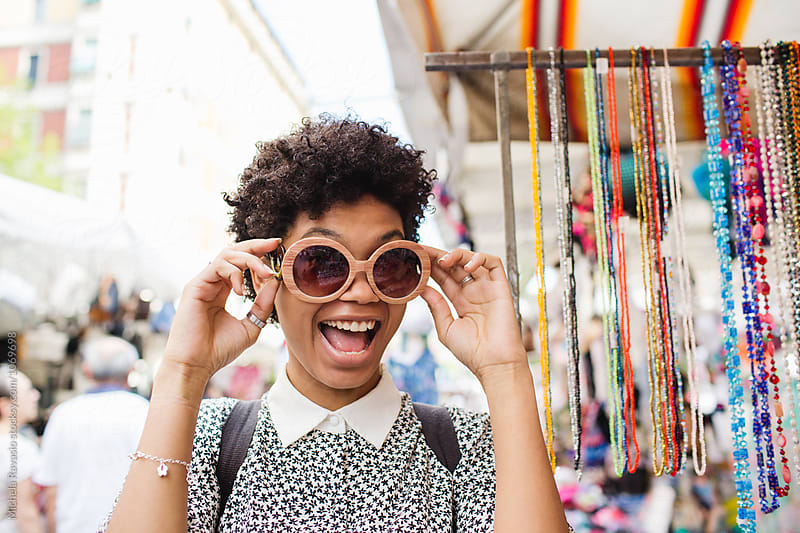 Happy woman wearing a pair of sunglasses at marketplace by michela ravasio for Stocksy United