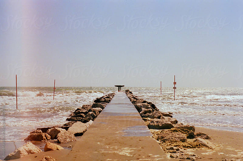A film photo of breakwater on Lido beach in Venice during storm by Anna Malgina for Stocksy United