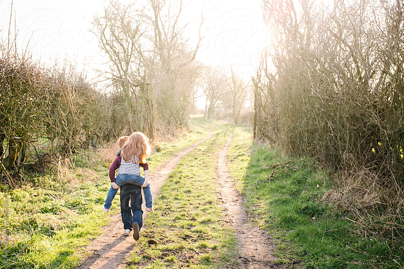 A little girl being given a piggy back lift by her brother during a walk in the countryside by Craig Holmes for Stocksy United