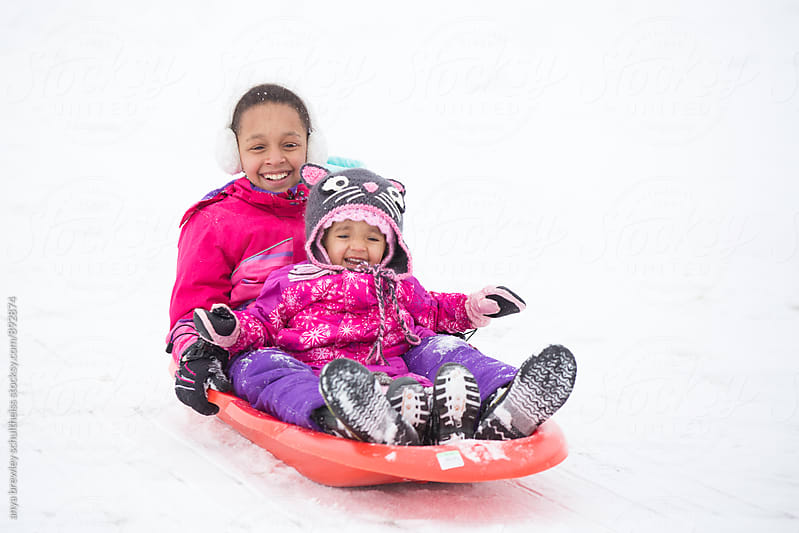 Portrait of kids wearing snowsuits having fun in the snow while tobogganing  by anya brewley schultheiss for Stocksy United