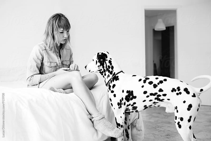 Girl at home with a Dalmatian dog by Lucas Ottone for Stocksy United