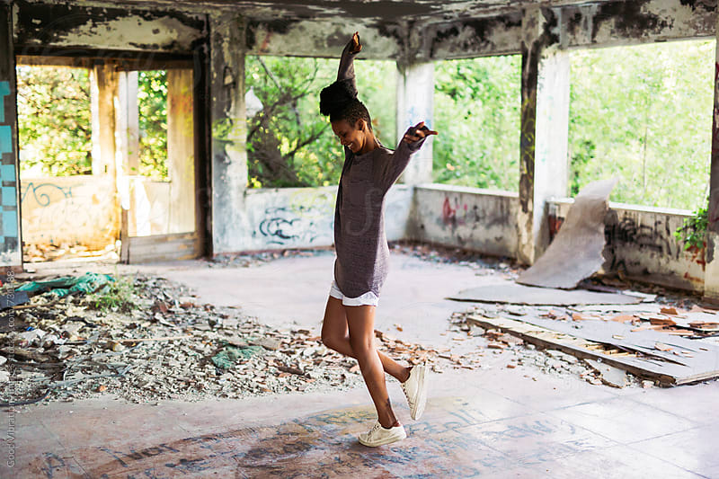 Woman with dreadlock having fun in an abandoned place by Good Vibrations Images for Stocksy United
