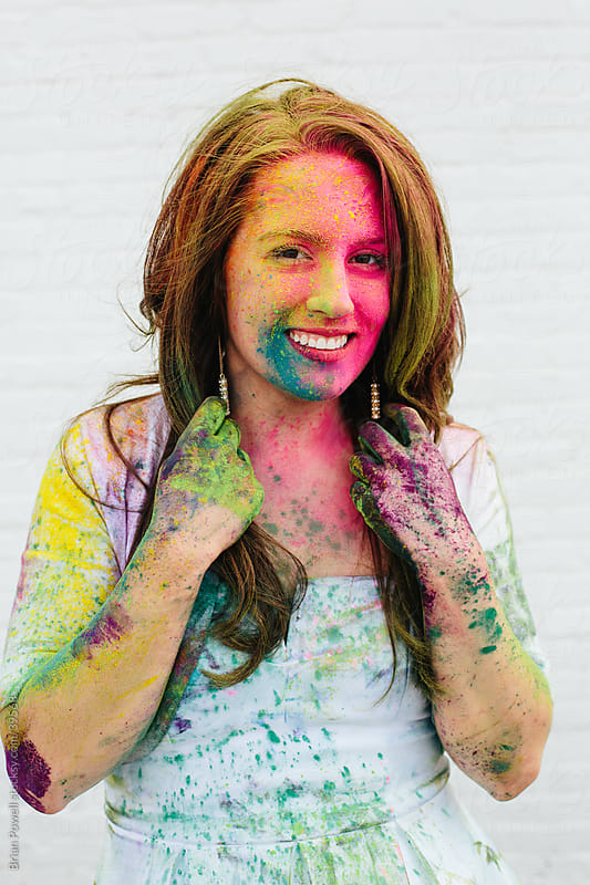 woman smiles during Holi by Brian Powell for Stocksy United