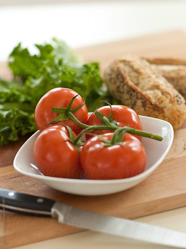 Tomatoes, lettuce and bread  by Daniel Hurst for Stocksy United