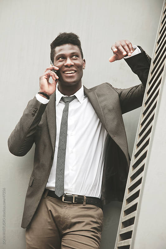 African young businessman talking on smartphone by BONNINSTUDIO for Stocksy United