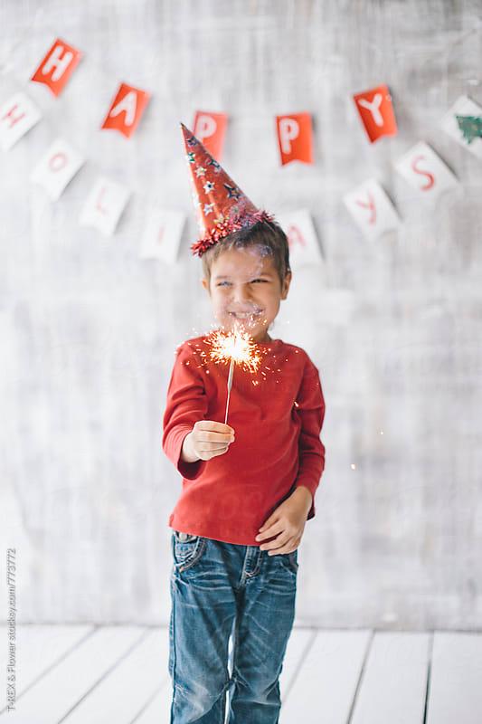 Little smiling boy holding sparkler by Danil Nevsky for Stocksy United