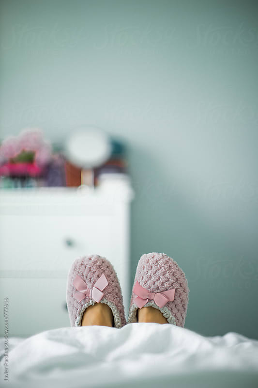 lying in bed with slippers by Javier Pardina for Stocksy United