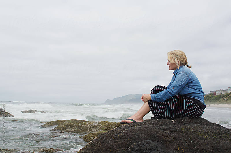 woman sitting on rock watching ocean by Tana Teel for Stocksy United