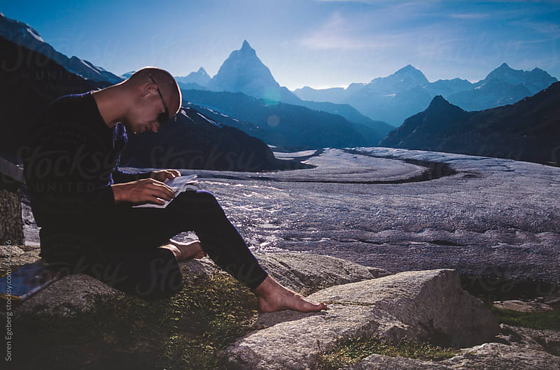 Young man sitting on a rock outside in the mountains near Matterhorn reading a guide book by Soren Egeberg for Stocksy United