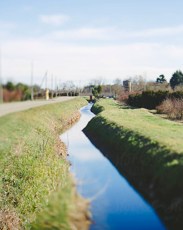Tilt-shift shot of landscape with stream in the italian countryside by Laura Stolfi for Stocksy United