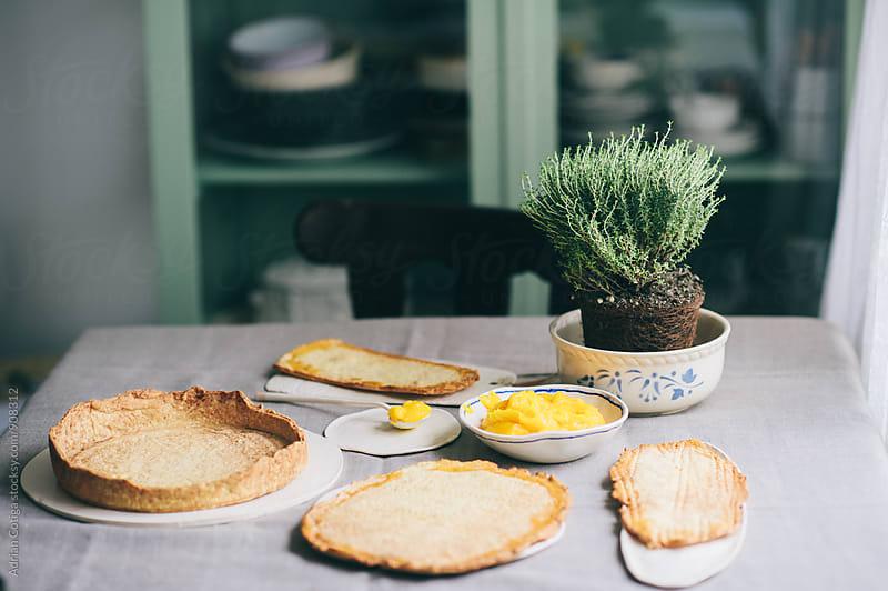 Preparing lemon tart; lemon filling homemade tart with thyme by Adrian Cotiga for Stocksy United