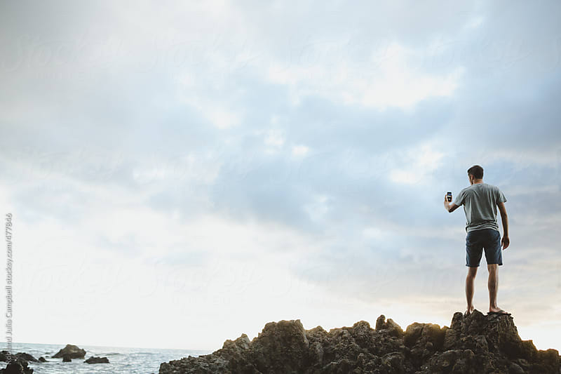 Young man taking cell phone photo at sunset on lava rocks  by Rob and Julia Campbell for Stocksy United