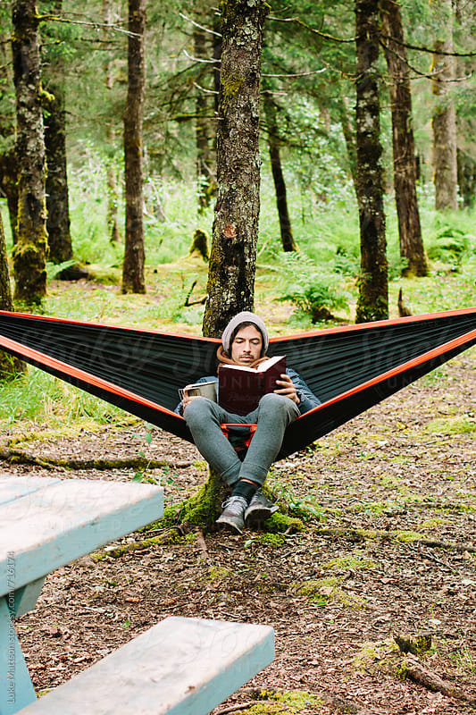 Young Man Sitting In A Hammock Reading A Book In the Woods by Luke Mattson for Stocksy United