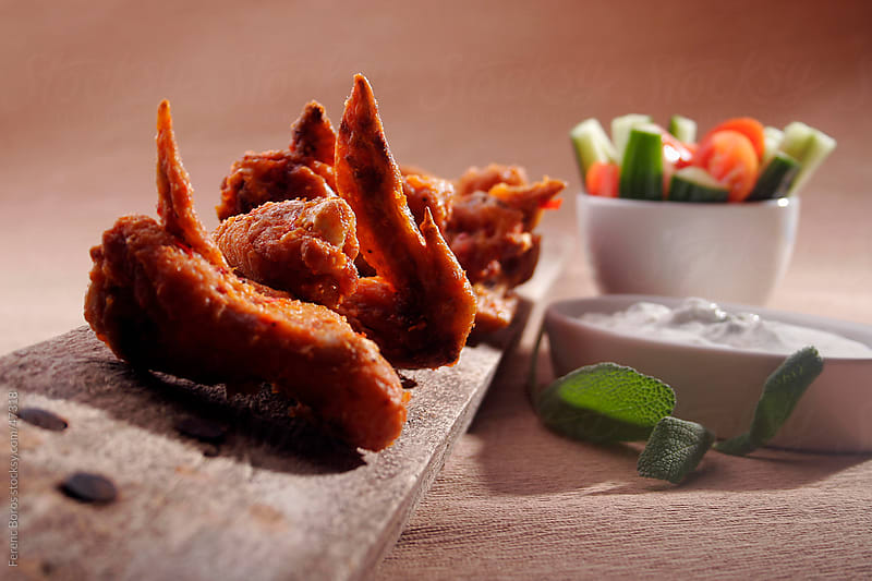 Buffalo chicken wings with vegetable sticks and cheese dip by Ferenc Boros for Stocksy United