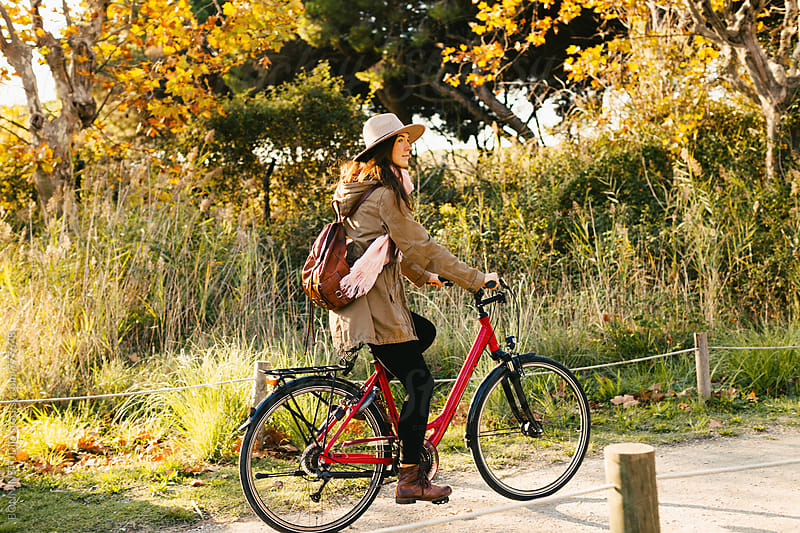 Hipster woman riding a bicycle in the forest. by BONNINSTUDIO for Stocksy United