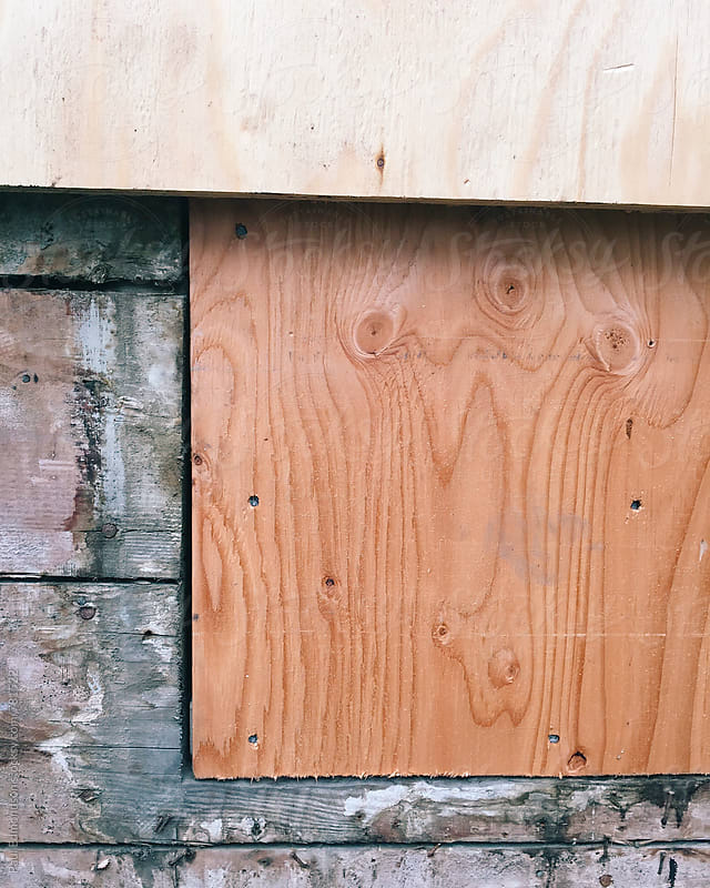 Plywood covering old wood siding and window on house exterior by Paul Edmondson for Stocksy United