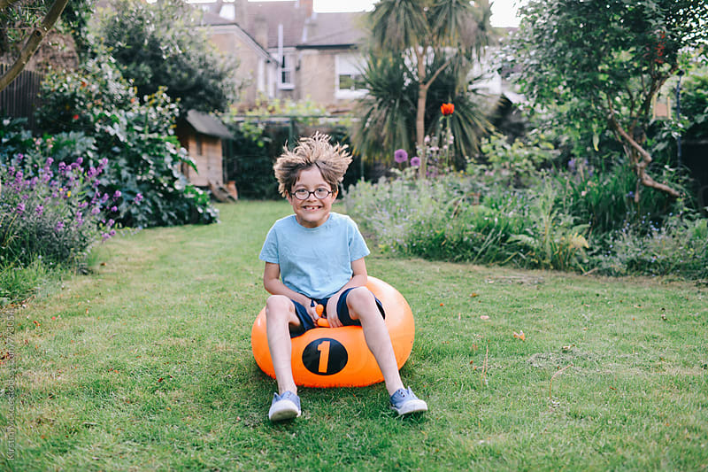 Boy grinning on space hopper by Kirstin Mckee for Stocksy United