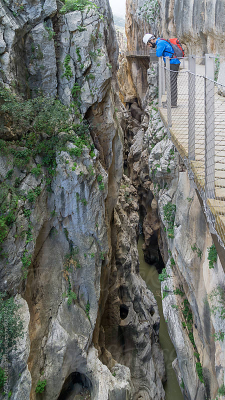 Climber looking down at the edge of a cliff in Caminito del Rey by ACALU Studio for Stocksy United