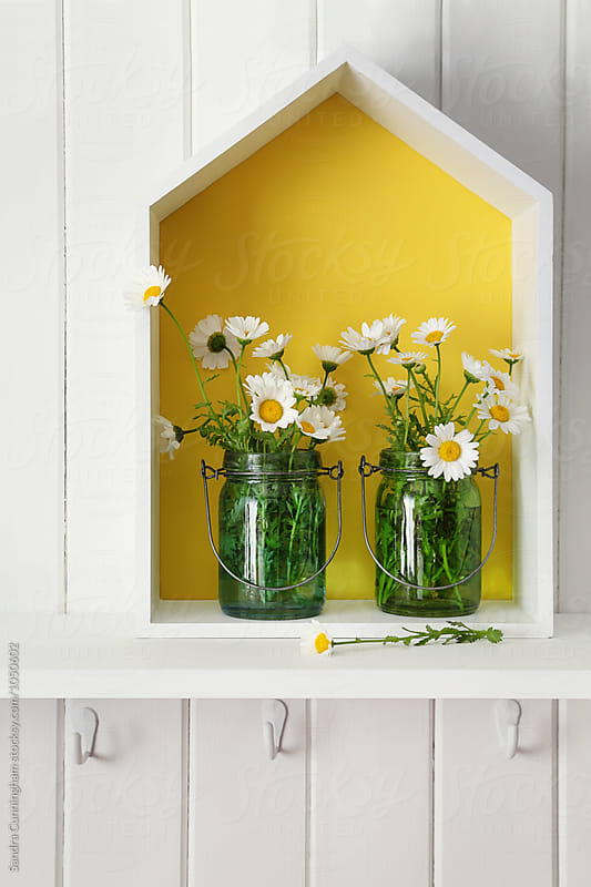 Daisies in jars on wooden house on shelf by Sandra Cunningham for Stocksy United