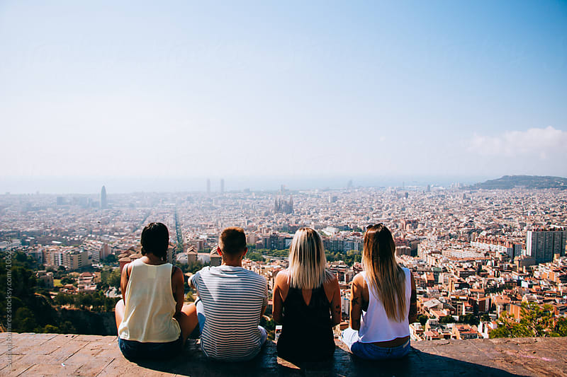 Group of friends sitting in a lookout with the city at your feet by Susana Ramírez for Stocksy United
