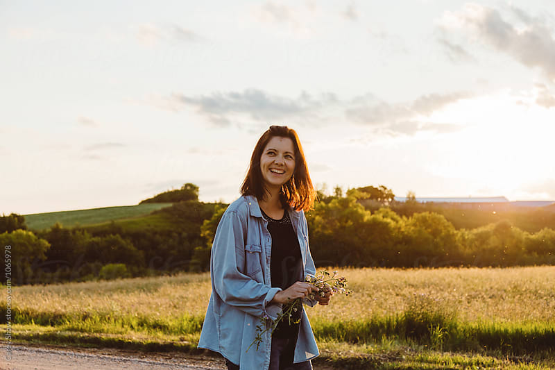 Smiling woman standing on countryside road at dusk by Carey Shaw for Stocksy United