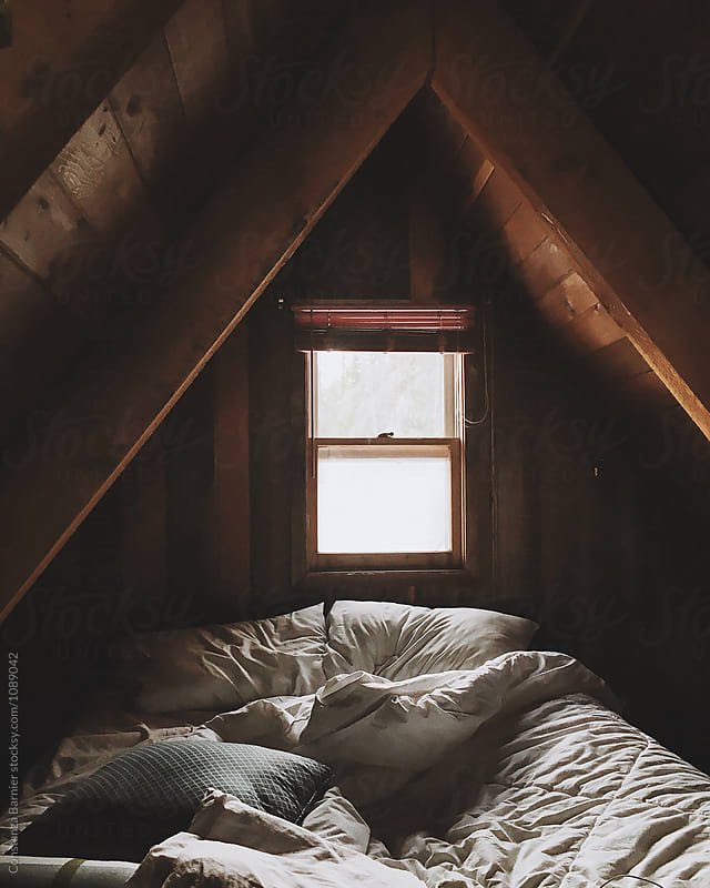 Cozy bed inside an A frame log cabin by Constanza Caiceo for Stocksy United