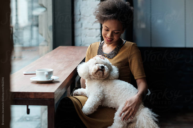 Young Woman Sitting at the Cafe with her Dog by Branislav Jovanović for Stocksy United