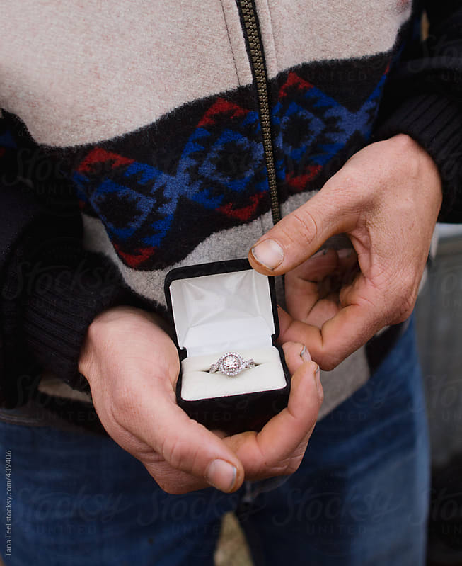 Young man holds diamond engagement ring by Tana Teel for Stocksy United