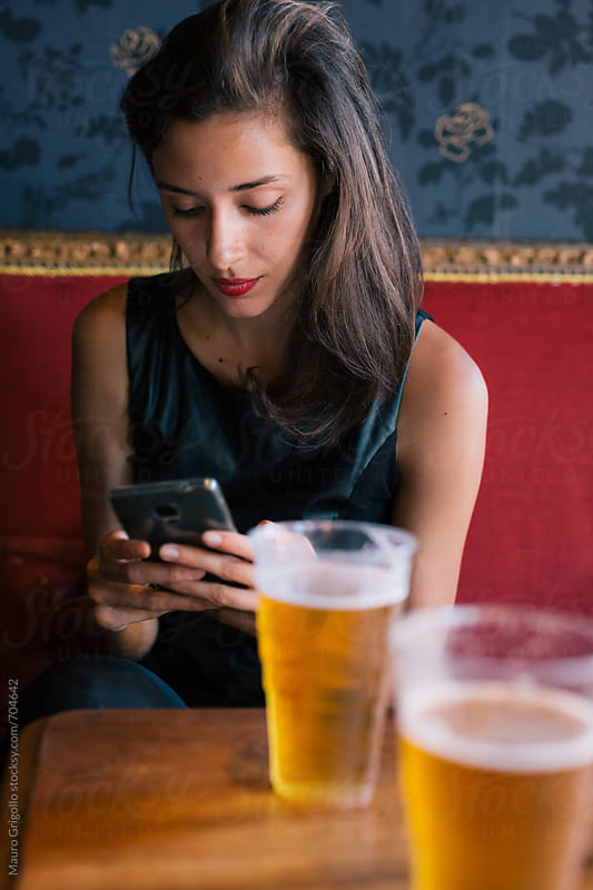 Woman drinking a beer in a Pub by Mauro Grigollo for Stocksy United