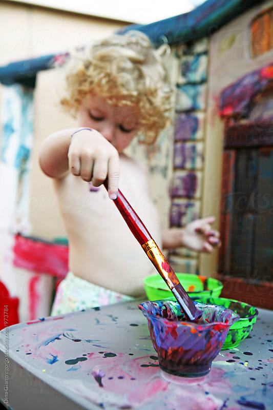 Curly Haired Toddler Painting by Dina Giangregorio for Stocksy United