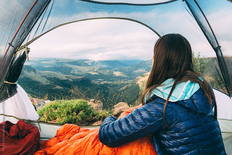 Hiker in her tent enjoying a mountain summit view by Micky Wiswedel for Stocksy United