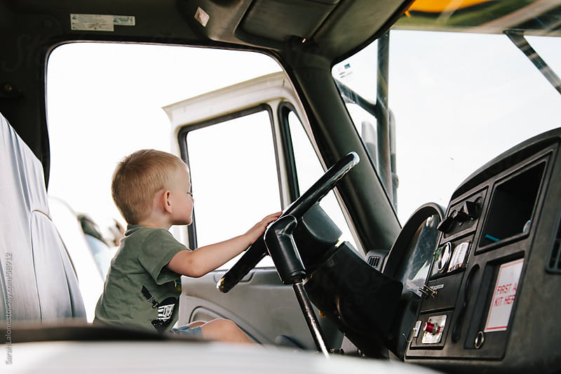 A little boy pretending to drive a large truck. by Sarah Lalone for Stocksy United