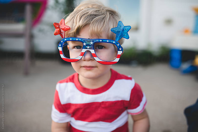 Young boy wearing patriotic glasses for fourth of july by Courtney Rust for Stocksy United