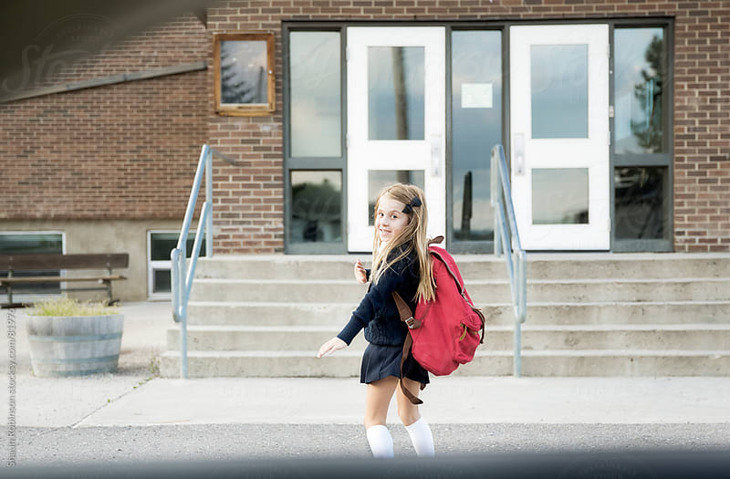 a girl waving back to a car as she runs to school by Shaun Robinson for Stocksy United